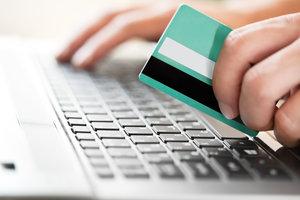 Zdjęcie [url=http://www.shutterstock.com/pl/pic-141354709/stock-photo-man-holding-credit-card-in-hand-and-entering-security-code-using-laptop-keyboard.html?src=tUxq6BxyYuOdg5IQchEXXA-1-4]klienta z kartą[/url] pochodzi z serwisu Shutterstock